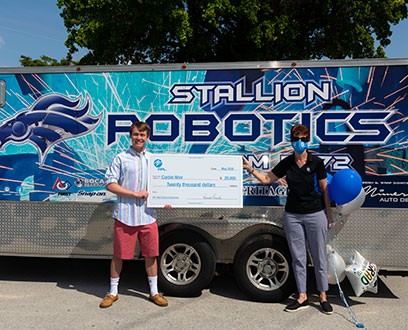 Robotics college scholarship with large check